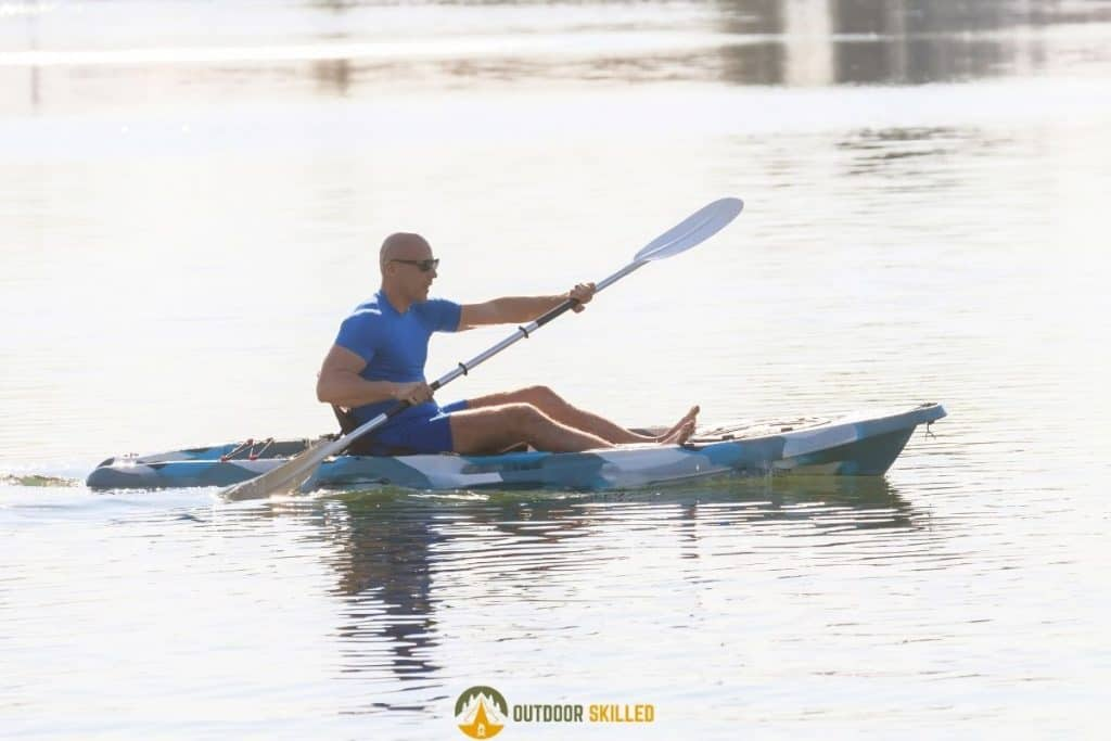 man paddling on an SOT kayak to show how to stay dry in a sit-on-top kayak